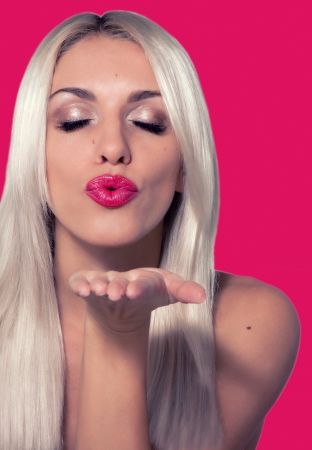 lipstick kiss: Beautiful blonde girl with red lipstick sends an air kiss Stock Photo