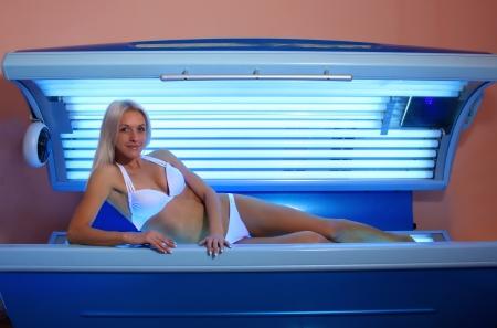 Beautiful slim blonde girl tans in the solarium