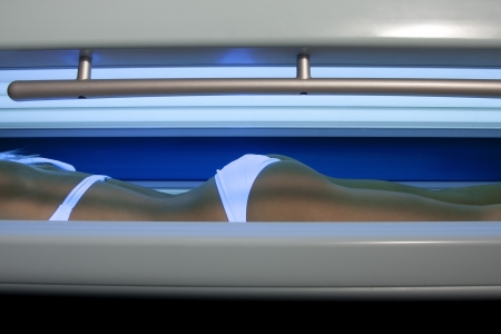 Beautiful slim blonde girl tans in the solarium