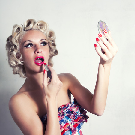 Stylized blonde lipstick red lipstick in the mirror. Pin up style. photo