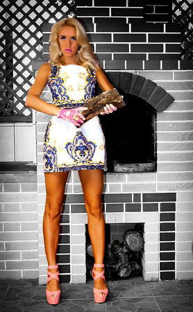 baby doll: Beautiful fashionable blonde at Russian stove with firewood