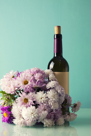 Bottle of red wine and a bouquet of wildflowers