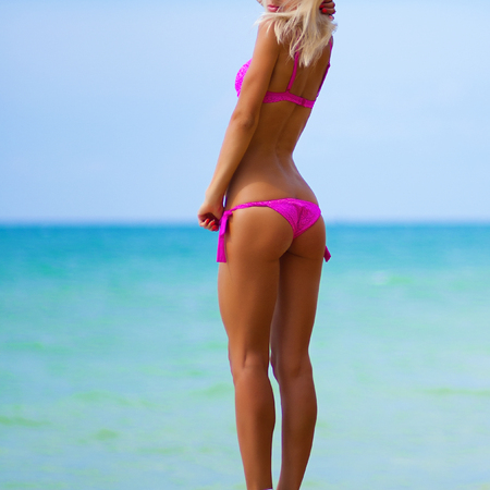 belles jambes: Une fille avec une belle silhouette élancée contre la mer