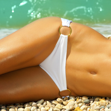 nude abs: A girl with a beautiful slender figure against the sea