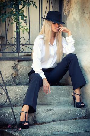 hair blond: Bella donna in vestito di un uomo seduto nel cortile, il volto coperto da un cappello. Archivio Fotografico