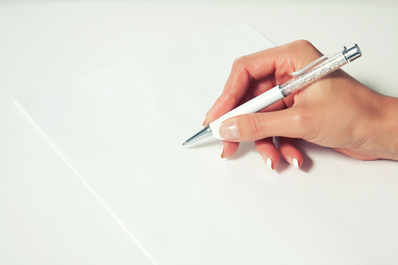Elegant female hand with French manicure writes beautiful pen on a blank sheet Stock Photo