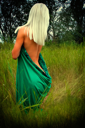 beautiful naked blonde girl in the grass, his back