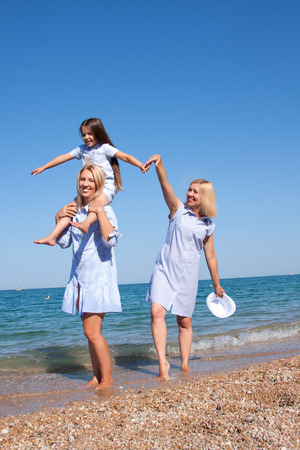 Beautiful Mom with daughter and grandmother relaxing and having fun on the beach Stock Photo