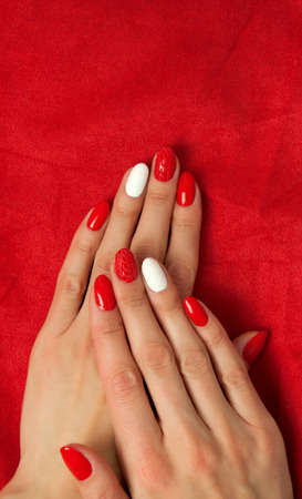 Female hands with a beautiful red manicure, on the background