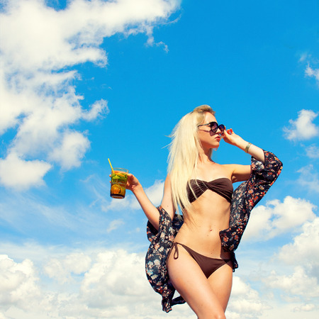 Beautiful lean blonde on the beach drinking a cocktail through a straw