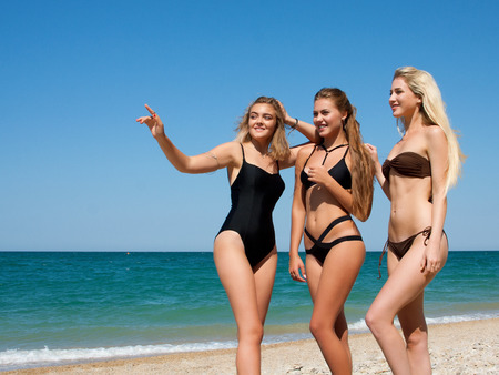Three beautiful girlfriends having fun on the beach