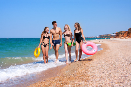Beautiful young people having fun on the beach near the sea with beach accessories