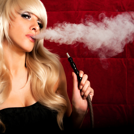 Beautiful woman smoking a hookah and smoke issues from the mouth Foto de archivo