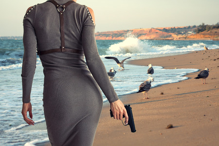 Beautiful woman in a dress holding a gun in her hand. View from the back.