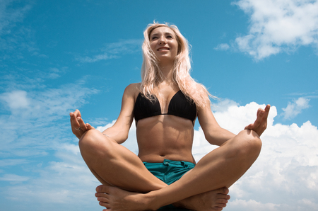 Young beautiful woman in a lotus position.