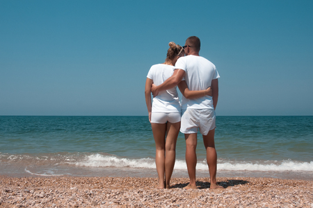 Back view of a romantic couple walking at beach during summer vacation