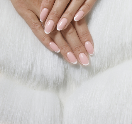 Stylish trendy female pink French manicure on white fur background. Banque d'images