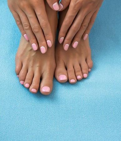 Soft female feet and hands with pedicure and manicure on a blue background