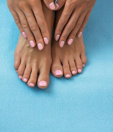 Zachte vrouwelijke voeten en handen met pedicure en manicure op een blauwe achtergrond