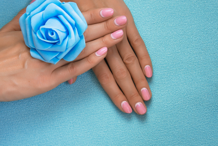 beauty delicate hands with manicure holding flower close up isolated on blue