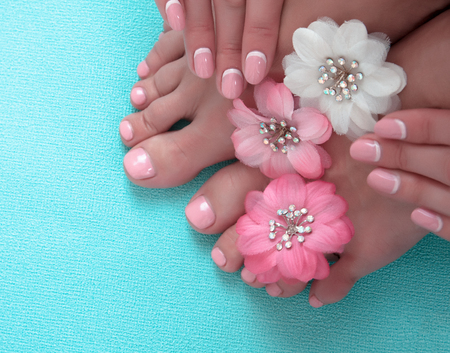 Beautiful pink manicure and pedicure with flowers on a blue background
