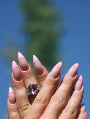 Long French nails with white manicure on a woman's hand with pink accessory on a nature background.