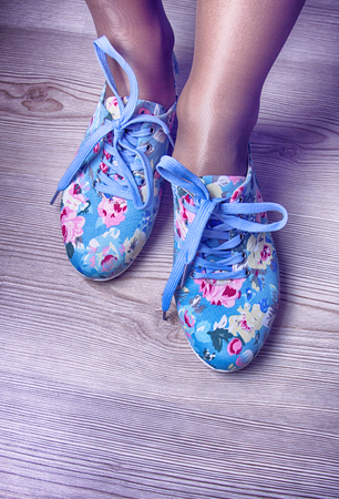 sneakers with floral print on the background of women's shirt with bright colors