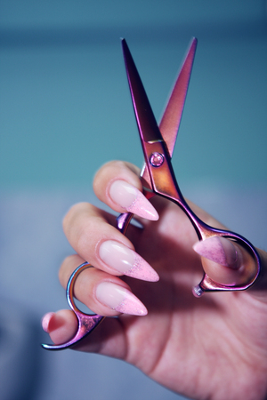 Female Hairdresser's Hands with long, well-groomed nails hold beautiful hair clippers. Imagens