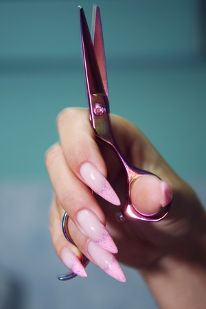 Female Hairdresser's Hands with long, well-groomed nails hold beautiful hair clippers. Banque d'images