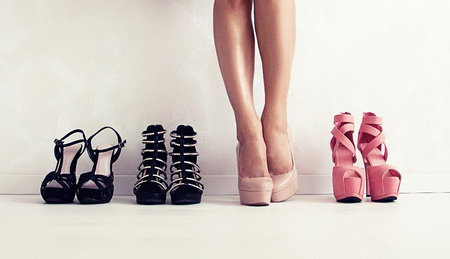 A slender woman in a beige dress chooses which shoes to dress