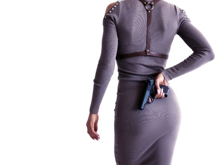 Beautiful woman in a dress holding a gun in her hand. View from the back. 写真素材