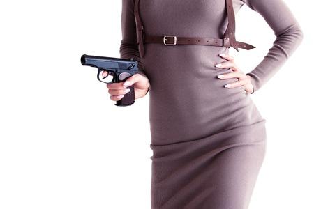 Belle femme vêtue d'une robe tenant un pistolet à la main.