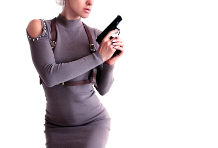 Beautiful woman in a dress holding a gun in her hand.