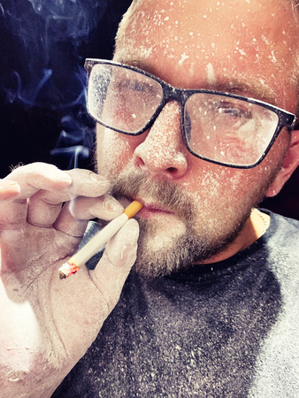 A young man in glasses with a face spattered with paint smokes a cigarette