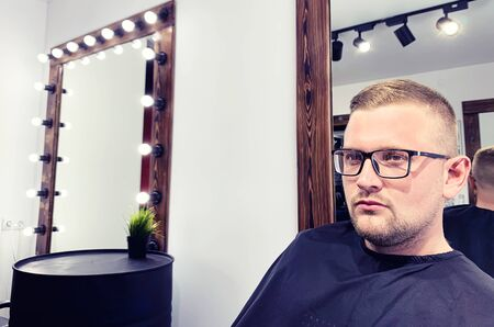 Male client getting haircut by hairdresser in a stylish beauty salon
