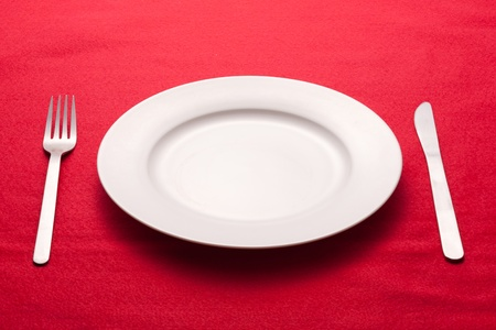 plate setting: White empty plate with fork and knife on a red tablecloth