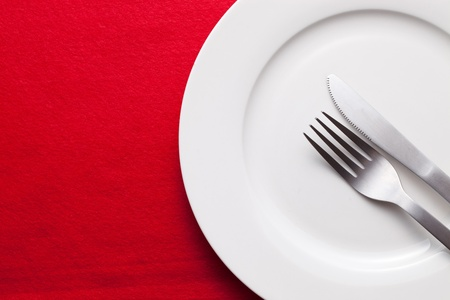 on the tablecloth: White empty plate with fork and knife on red tablecloth Stock Photo