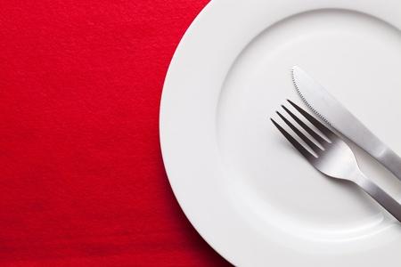 Witte lege plaat met vork en mes op rode tafelkleed Stockfoto