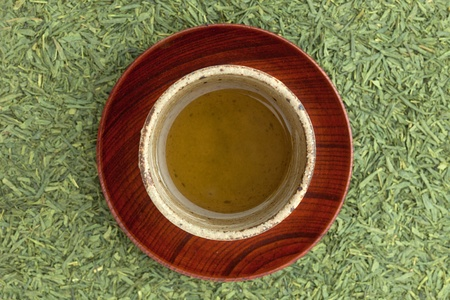 a cup of green tea on tea leaves  photo