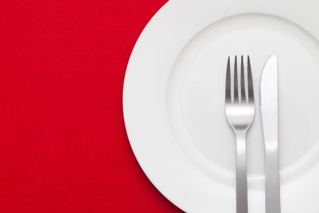 plate setting: White empty plate with fork and knife on red tablecloth  Stock Photo