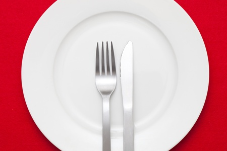 White empty plate with fork and knife on red tablecloth  photo