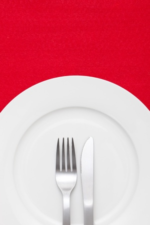 flatware: White empty plate with fork and knife on red tablecloth  Stock Photo