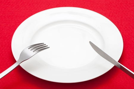 red tablecloth: White empty plate with fork and knife on red tablecloth  Stock Photo