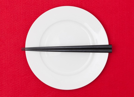 red tablecloth: White empty plate with chopsticks on red tablecloth