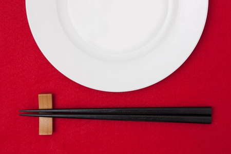 flatware: White empty plate with chopsticks on red tablecloth