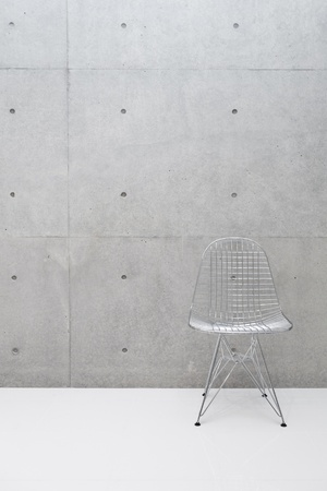 old home office: wire chair and concrete wall