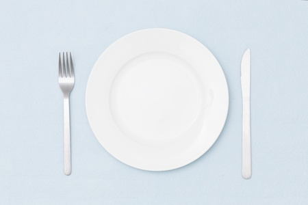 White empty plate with fork and knife on light blue tablecloth  photo