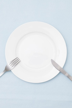 plate setting: White empty plate with fork and knife on light blue tablecloth  Stock Photo