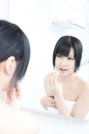 young woman applies makeup in front of a bathroom mirror Stock Photo - 14001612