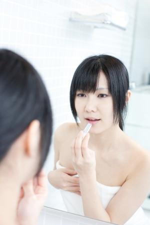 young woman applies makeup in front of a bathroom mirror  Stock Photo - 14001543